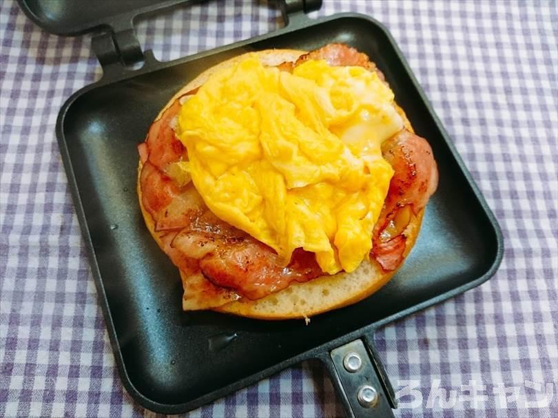 ベーグルを具だくさんのサンドイッチにしてホットサンドメーカーで焼く(ベーコン・スクランブルエッグ・とろけるチーズ入り)