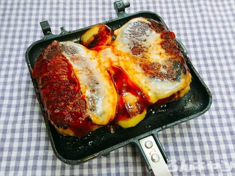 ホットサンドメーカーで焼いたハンバーグとじゃがいもにとろけるチーズをのせてケチャップと中濃ソースをかける