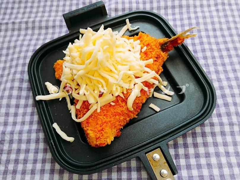 ホットサンドメーカーで焼く前のアジフライにとろけるチーズを山盛りにした状態