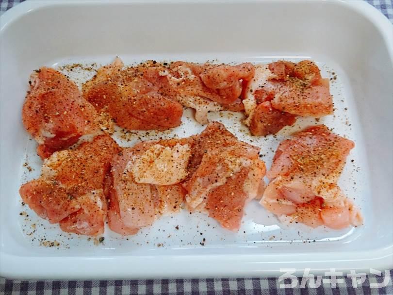 バットに入れた唐揚げ用の鶏肉に下味のマキシマムをかける