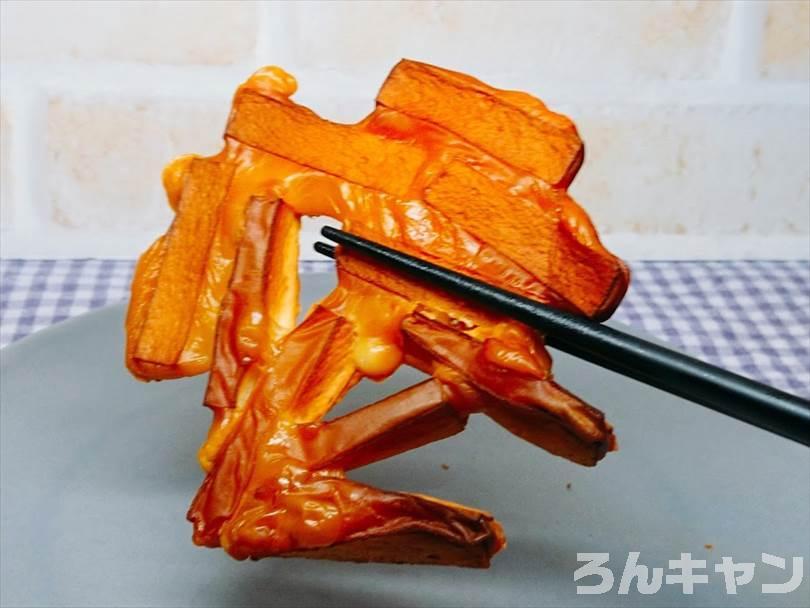 燻製したチーズ鱈を箸で持ち上げる様子